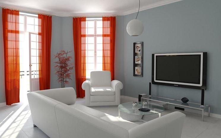 Soggiorno con colori tendenti al bianco e al grigio con tende color rosso.