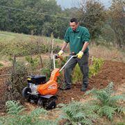 Agricoltore al lavoro con la motozappa