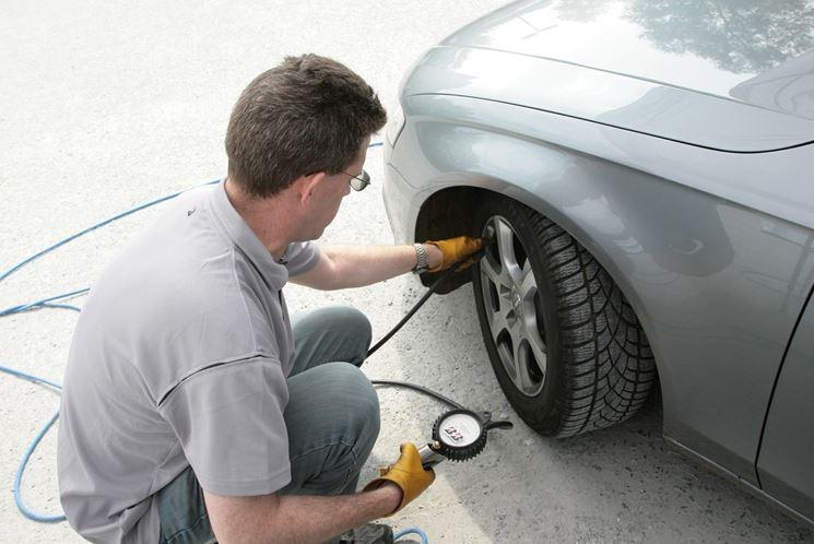 Un uomo controlla la pressione degli pneumatici