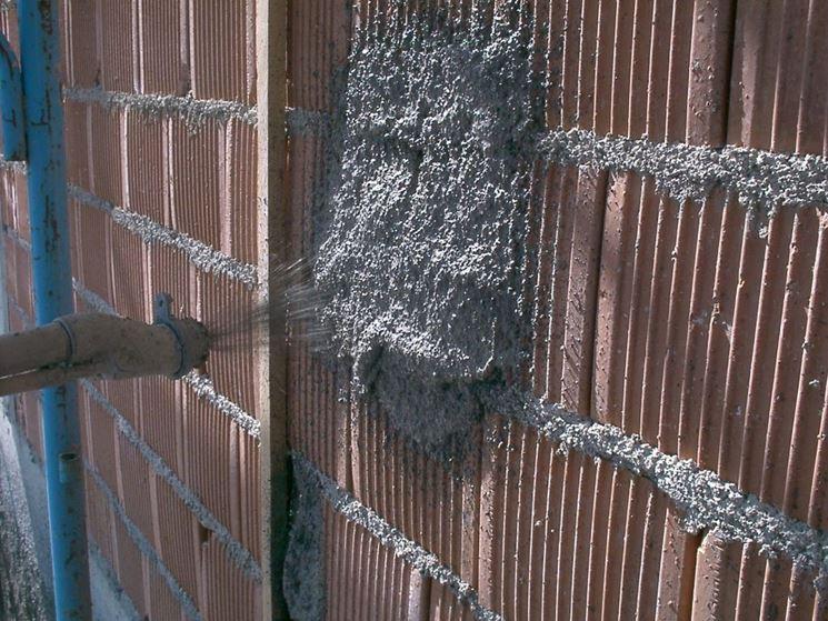 Applicazione a spruzzo di intonaco su muratura in mattoni forati