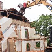 Demolizione di una casa con l'ausilio di mezzi meccanici
